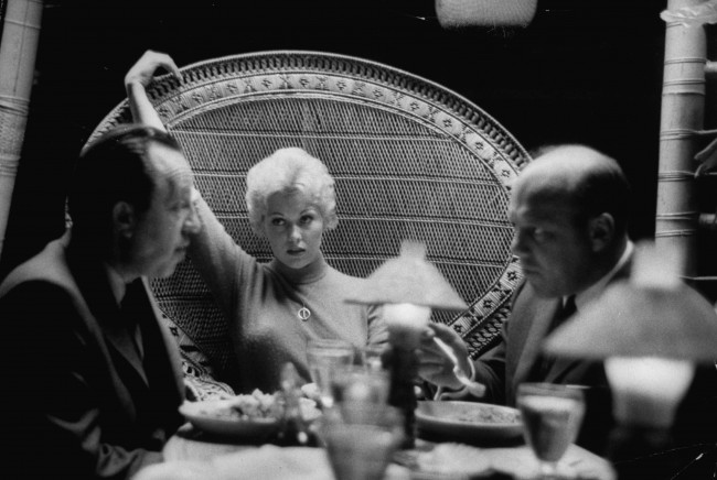 Actress Kim Novak sitting with agents Al and Wilt Melnick, hotly discussing her blossoming movie career. (Photo by Leonard Mccombe//Time Life Pictures/Getty Images)